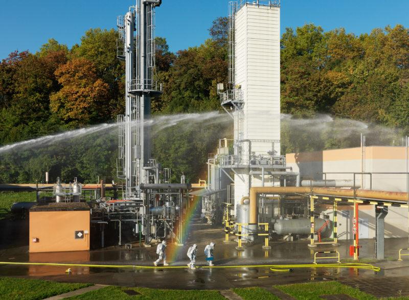 Reportagefotografie: Bei einer Übung an einem Gasverteiler gehen drei Feuerwehrleute in silberner Hitzeschutzkleidung und Werkzeug nach vorne, während über ihnen ein Löschmonitor Wasser zum angenommenen Brandherd bringt.