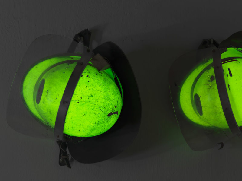 editorial photography: Firefighter helmets are hanging on a wall. They glow green in the dark. On the paint you can see the traces of past operations.