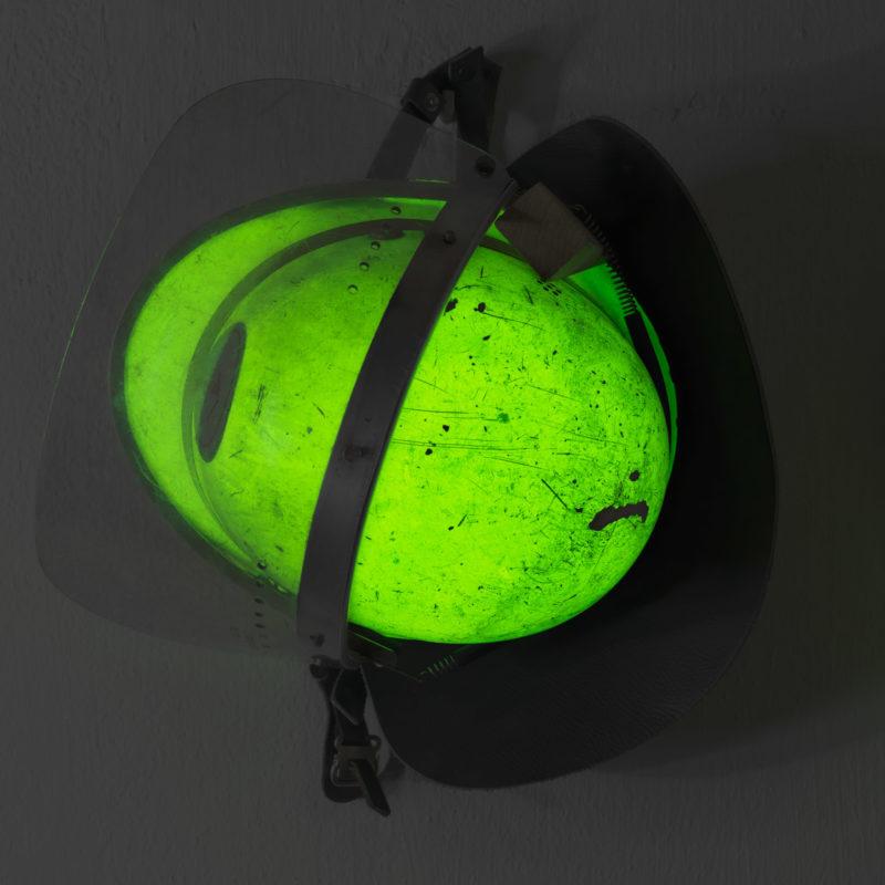 Luftaufnahmen und Drohnenfotografie: Reportagefotografie: Feuerwehrhelme hängen an einer Wand. Sie leuchten im Dunkeln grün. Auf dem Lack sieht man die Spuren vergangener Einsätze.