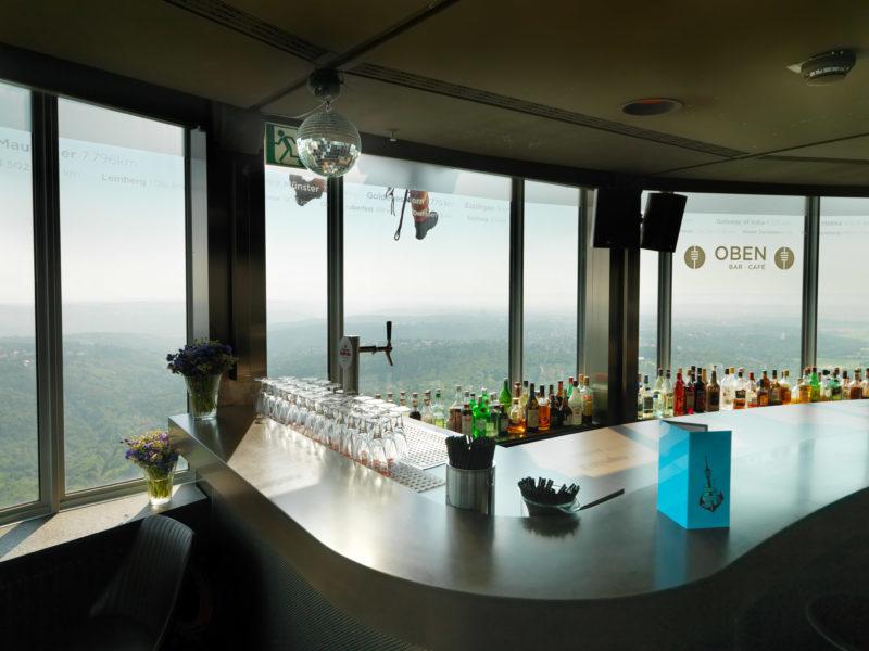 Reportagefotografie: Übung der Feuerwehr-Höhenretter am Stuttgarter Fernsehturm. Von der Bar im Turm aus sieht man vor dem Fenster die Stiefel eines sich aus ca. 180 Metern Höhe abseilenden Retters.