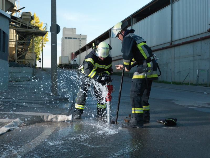 Reportagefotografie: Zwei Feuerwehrmänner bringen an einem Hydrant im Boden ein Standrohr an, an dem dann Löschschläuche angeschlossen werden können. Wasser spritzt.