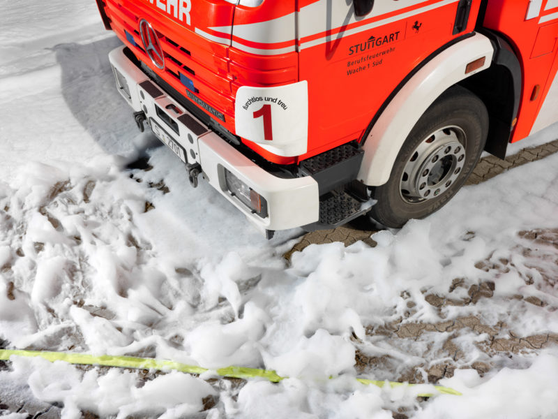 editorial photography: Around a fire engine, white fire foam is spread on the floor.