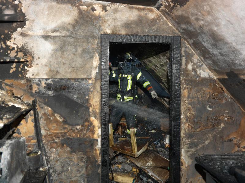 Reportagefotografie: Feuerwehrmann beim Nachlöschen in einem ausgebrannten Dachstock eines Wohnhauses. Alles ist schwarz verkohlt und auch das ganze Mobiliar ist zerstört.