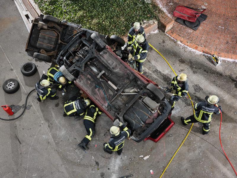Reportagefotografie: Feuerwehrleute üben die Bergung von eigeklemmten verletzten Insassen eines verunglückten PKW. Das Foto ist senkrecht von oben aufgenommen und man sieht in der Mitte den Boden des auf dem Dach liegenden Fahrzeuges, das von Feuerwehrleuten umringt ist.