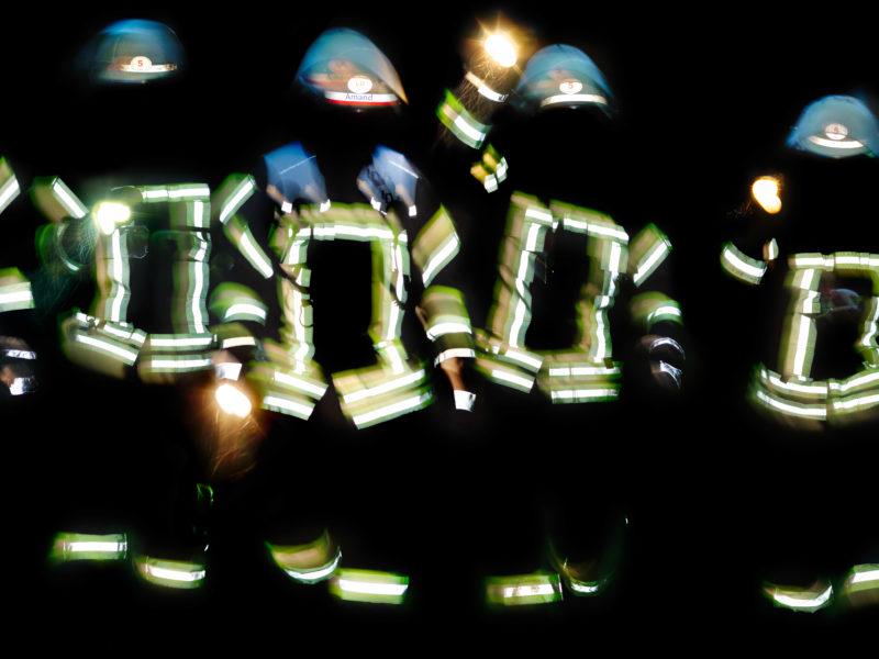 Reportagefotografie: Feuerwehrleute bei Nacht. Die Signalstreifen auf den Jacken und die Helme reflektieren hell, während die Gesichter im Dunkeln bleiben.