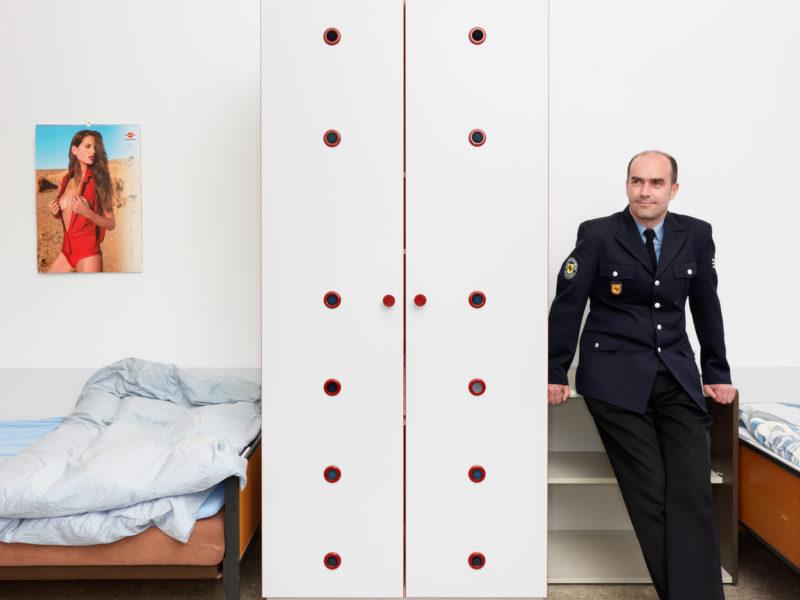 Reportagefotografie: Ein Feuerwehrmann in Uniform in einem der Schlafräume der Feuerwache. Durch die 24 Stunden-Schichten werden die Betten von mehreren Beamten genutzt.