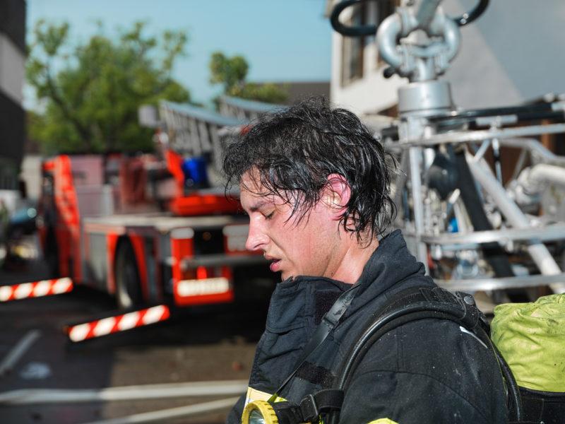 Reportagefotografie: Ein Feuerwehrmann, nachdem er bei seinem Löscheinsatz in einem brennenden Haus abgelöst wurde. Schweiss bedeckt seinen Kopf.