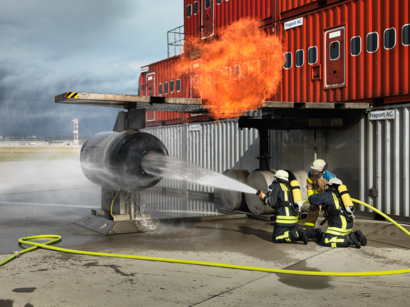 editorial photography: During a major exercise at the airport, firefighters spray water into the dummy of an aircraft turbine after a flame explosion has risen from there.