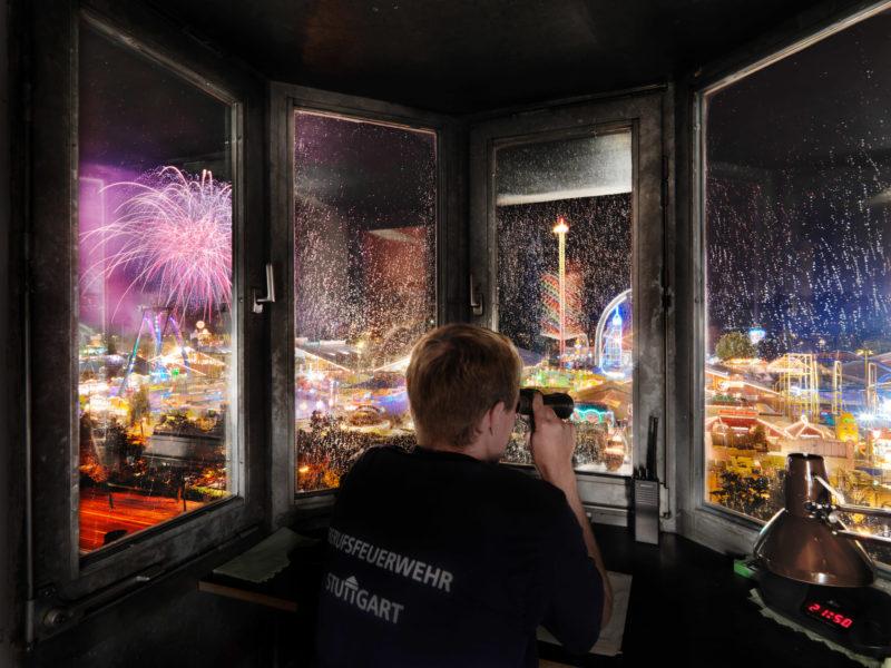 Reportagefotografie: Ein Stuttgarter Berufsfeuerwehrmann überwacht nachts aus einer Kanzel in der benachbarten Feuerwache das Cannstatter Volksfest, während dort das Feuerwerk gezündet wird.