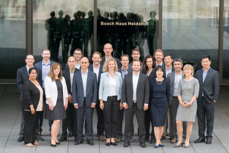 Group photo: The members of a department stand together in front of a company building. They are reflected as silhouettes in the glass panes behind them.