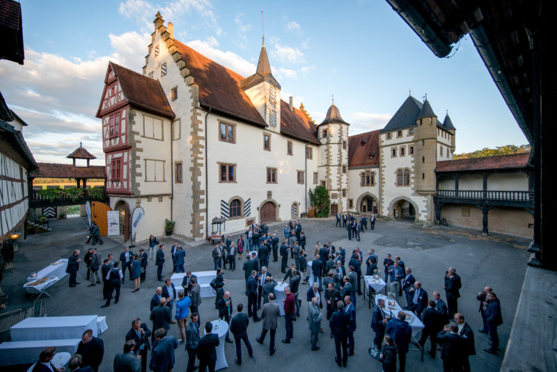 Editorial photography as event photography and fair photography: Company event at the Götzenburg Jagsthausen. View into the castle courtyard, where the employees stand in groups and talk to each other over a drink.