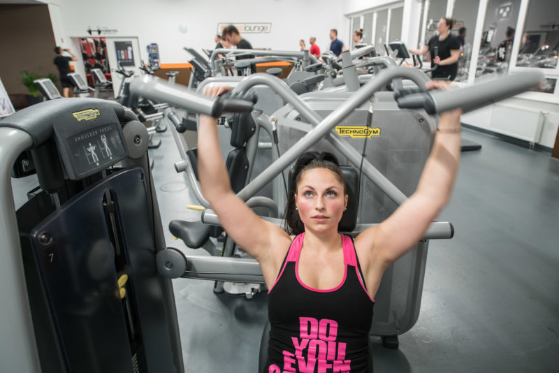 Employees photography: A woman trains her arm muscles in her free time in the gym.