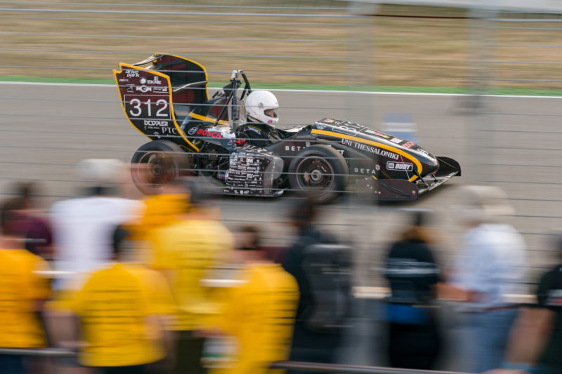 Editorial photography: Formula Student Germany: A racing car during acceleration measurement. In the foreground, blurred spectators due to the camera being pulled along with the moving racing car.