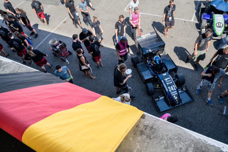 Editorial photography: Formula Student Germany: A racing car is brought from the sun into the pits together. Above the gate hangs the German flag.