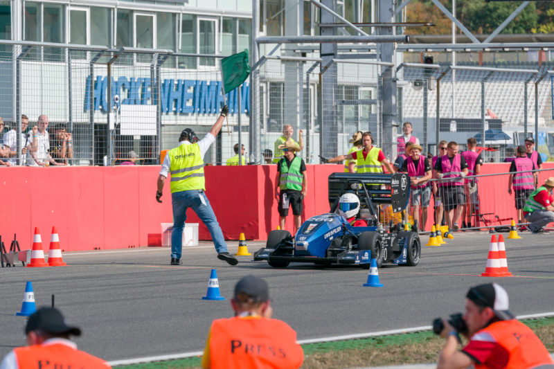 Editorial photography: Formula Student Germany: Start for speed measurement. The start flag is waved. Members of the team and the competition are watching in suspense.