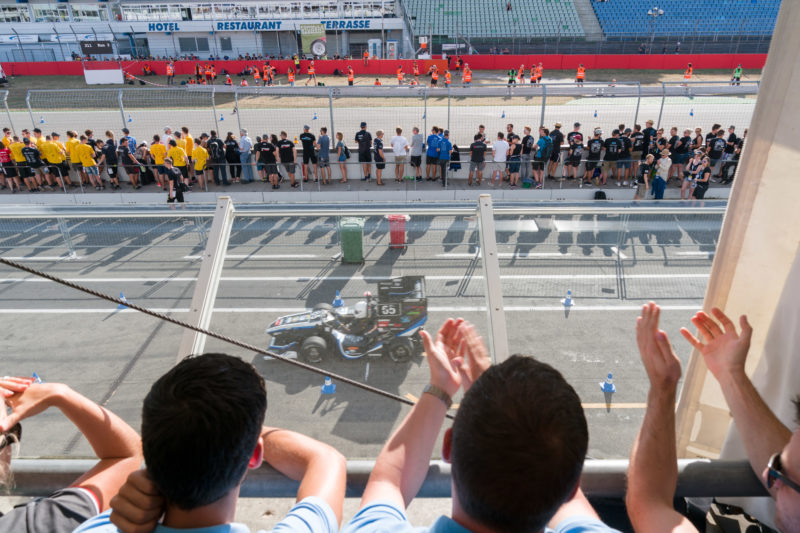 Editorial photography: Formula Student Germany: View over the shoulder of applauding spectators. Below you can see the race track, other spectators and helpers, and a race car.
