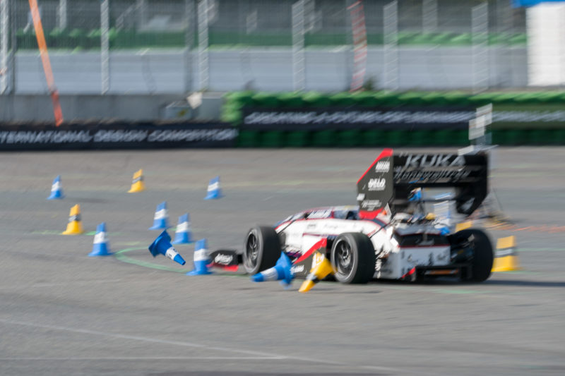 Editorial photography: Formula Student Germany: A racing car strays off the track on the circuit and guiding cones fly through the air. The picture is deliberately blurred to show the dynamics.