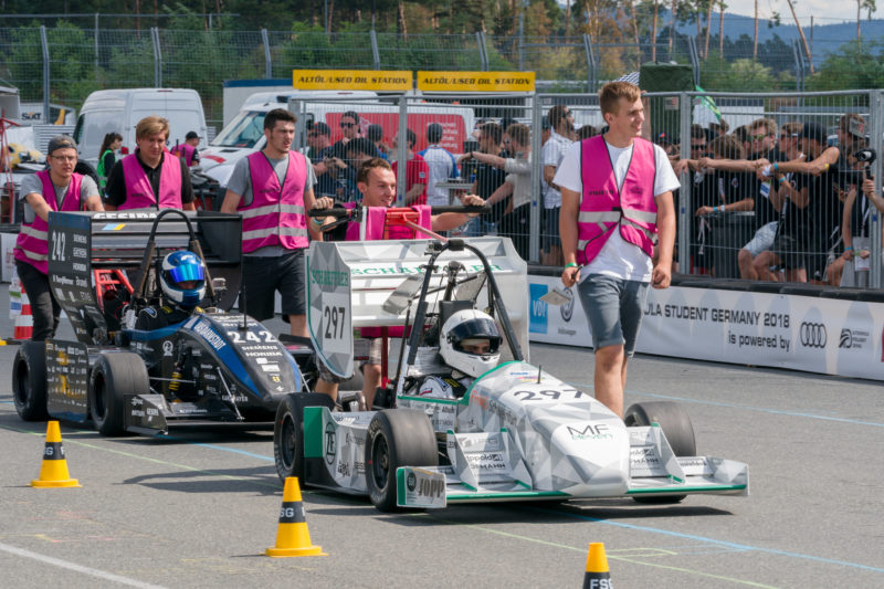 Editorial photography: Formula Student Germany: Two race cars of the combustion class are brought to the start. Team members accompany them on foot and push.