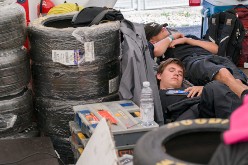 Editorial photography: Formula Student Germany: Two students are lying asleep in the pits during a break in the race between stacked tyres and material.