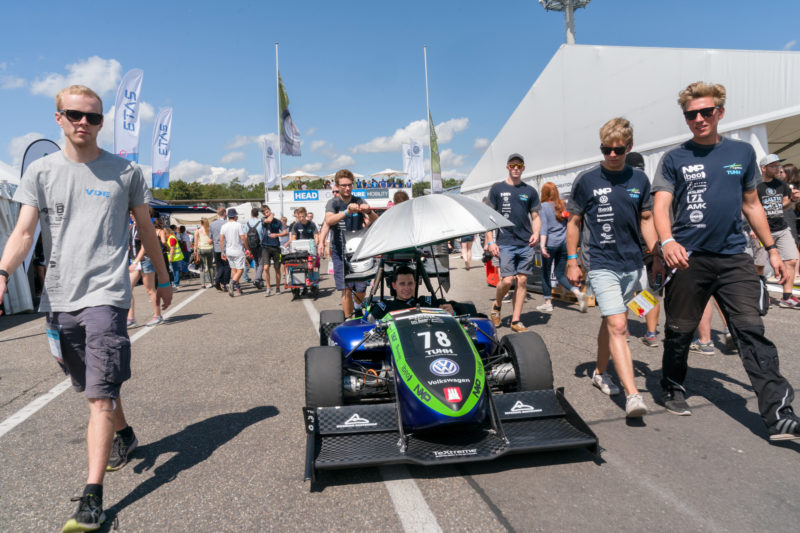 Editorial photography: Formula Student Germany: On the way to a race, the driver in the cockpit in a protective suit is protected from the heat of the sun by his team colleagues with an umbrella.