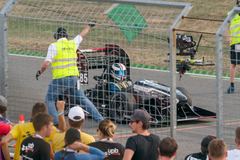 Editorial photography: Formula Student Germany: A racing car starts its run at the race track for acceleration measurement. Spectators are in the foreground and a rope camera is to accompany his race.
