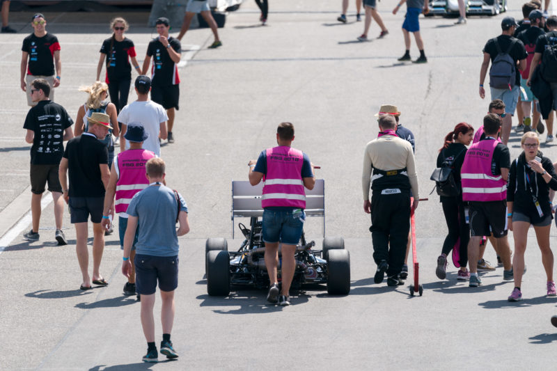 Editorial photography: Formula Student Germany: Everywhere on the paths between the pits and the racetracks, students and racing cars pushed by them are on the move.