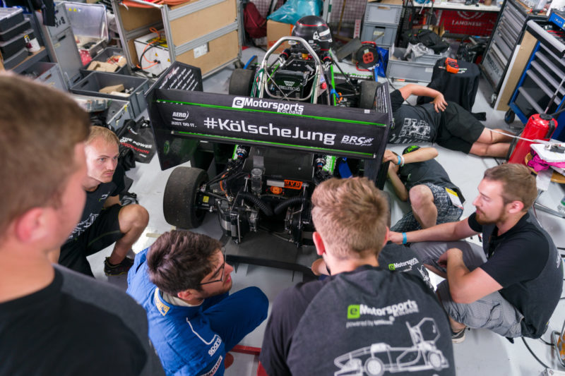 Editorial photography: Formula Student Germany: An electric racing car is maintained in the pit by the team. The students have surrounded the vehicle and everyone is working on their  position.