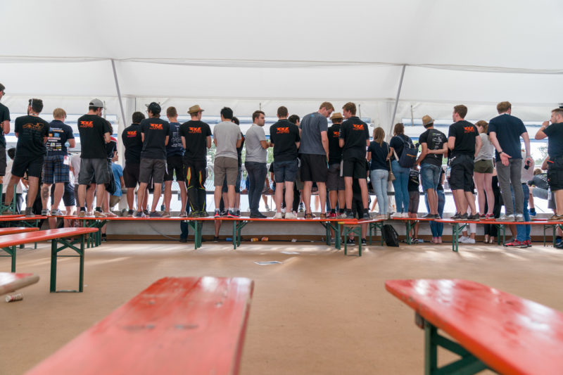 Editorial photography: Formula Student Germany: Most team members are men. Nevertheless there are also some women among the audience. Many stand on benches to see better.