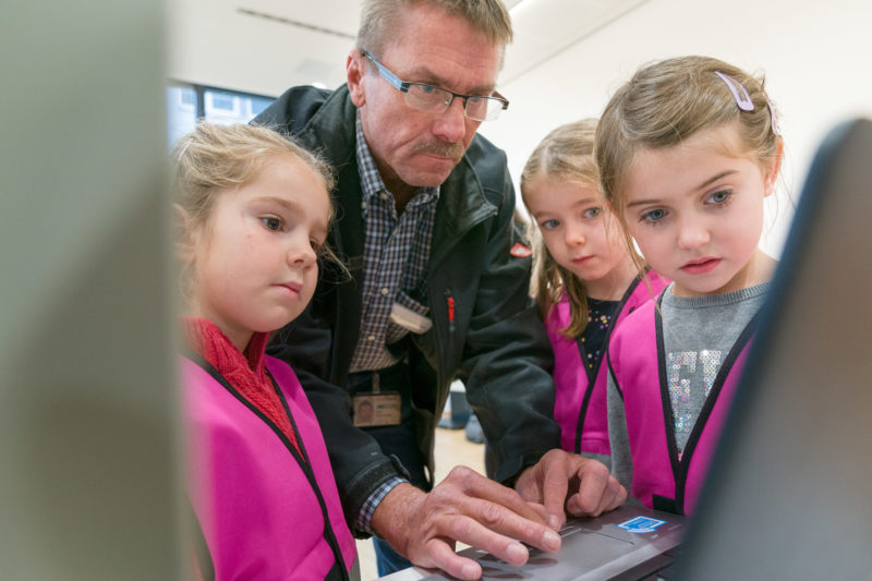 Editorial photography, subject learning and education: Three little girls watch  in a company a technician working on a notebook to control a machine on a tinkerer