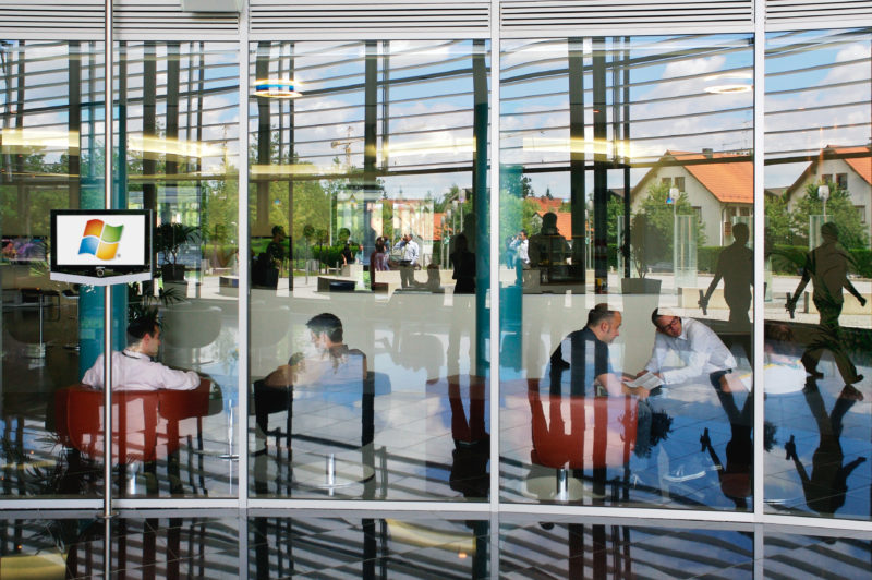 Architectural photography:  In the entrance area of a modern office building, the people in the foyer and in a lounge merge with the architecture of the glass facade and the buildings in the neighbourhood that are reflected in it.