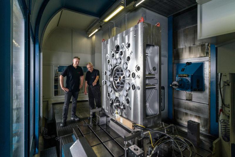 Industriefotografie: Zwei Mitarbeiter in der Werkzeugmaschinelindustrie begutachten innerhalb einer riesigen Fräskabine ein über 2 Meter großes Werkstück, das darin präzise bearbeitet werden soll. Rechts ist ein Fräskopf sichtbar.