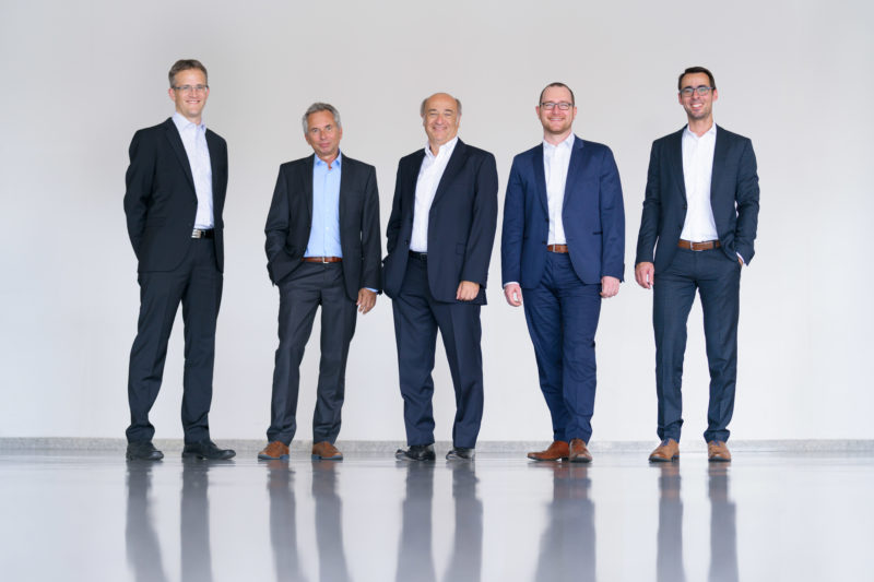 Group photo: The 5 executives of a company in full body portrait in front of a light neutral background and on a light reflecting floor.