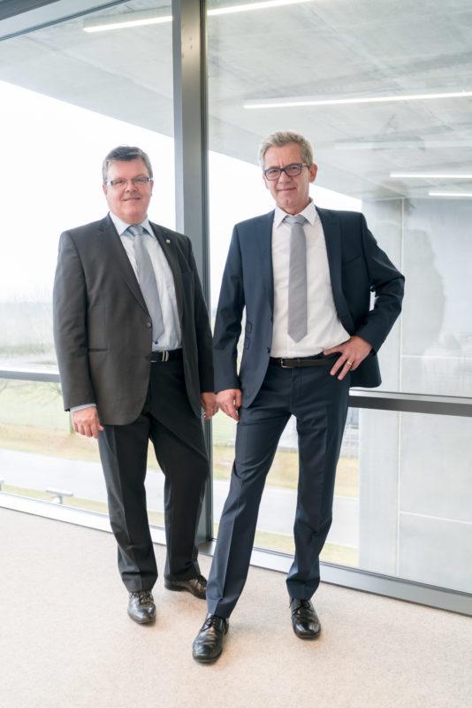 Managerportrait: Zwei männliche Führungskräfte, perfekt gekleidet in Anzügen und beide mit grauer Krawatte. Es ist ein Doppelportrait in ganzer Figur. Sie gehen vor einer bis zum Boden gehenden Glaswand im großen Konferenzraum der Firma. Außen sieht man die moderne Architektur des Gebäudes.