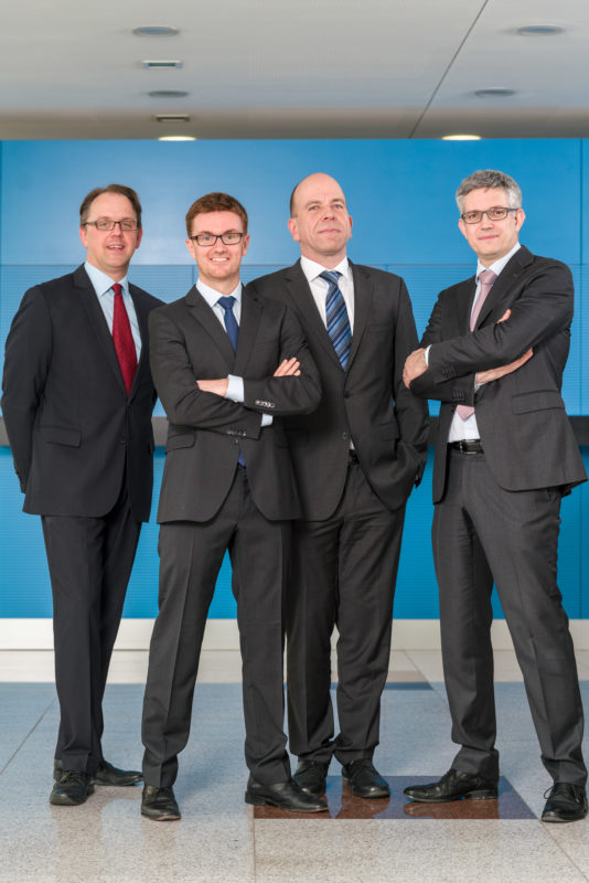 Group photo:  Four executives in the foyer of their company. Full body group picture with suit and tie.