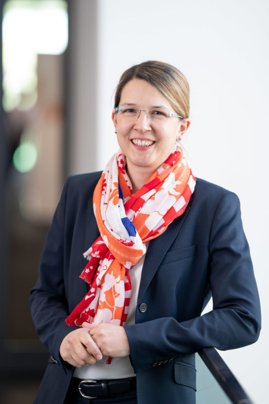 Executive portrait: A young woman with glasses and coloured scarf laughs into the camera. In the background you can see beautiful blurred company surroundings.