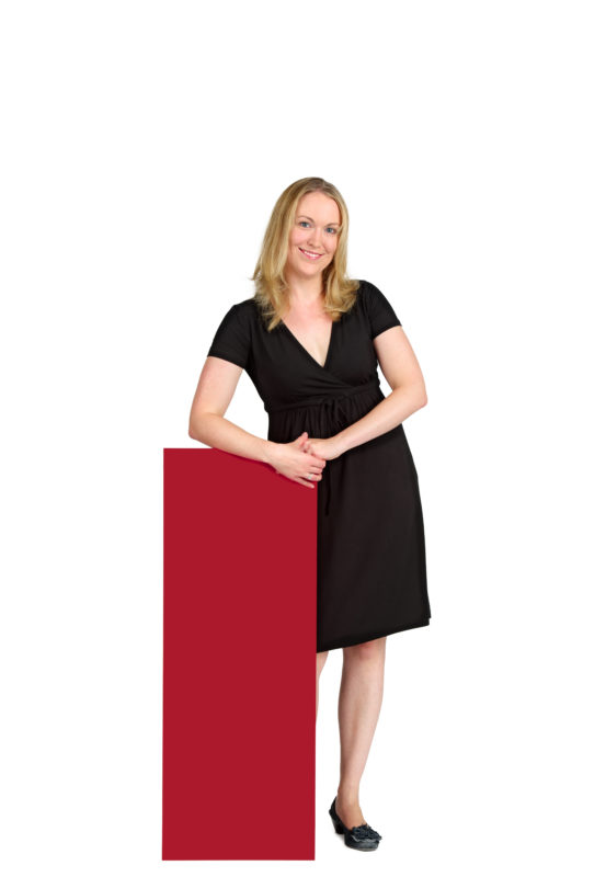Employees photography: For a personnel campaign of a vehicle manufacturer, employees pose with a red sign against a white background. The photos are full body shots and each person acts differently in front of the camera. Here a woman just stands there relaxed.