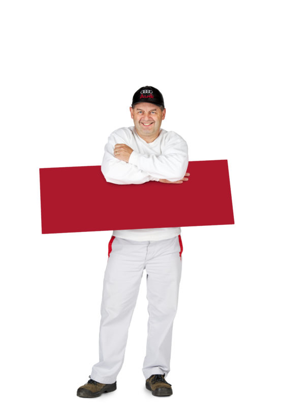 Employees photography: For a personnel campaign of a vehicle manufacturer, employees pose with a red sign against a white background. The photos are full body shots and each person acts differently in front of the camera. Here an employee has clamped his sign under his arms.