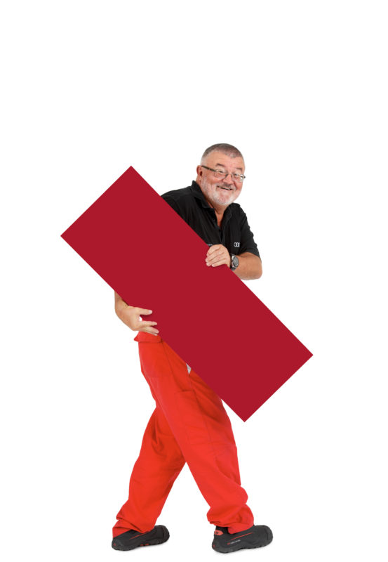 Employees photography: For a personnel campaign of a vehicle manufacturer, employees pose with a red sign against a white background. The photos are full body shots and each person acts differently in front of the camera. Here an employee walks through the picture with the sign.
