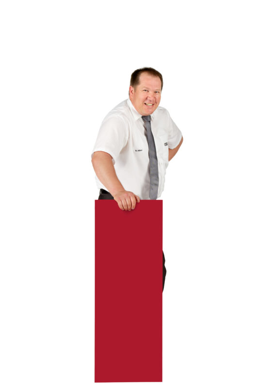 Employees photography: For a personnel campaign of a vehicle manufacturer, employees pose with a red sign against a white background. The photos are full body shots and each person acts differently in front of the camera. Here an employee has placed his sign vertically in front of him on the floor.