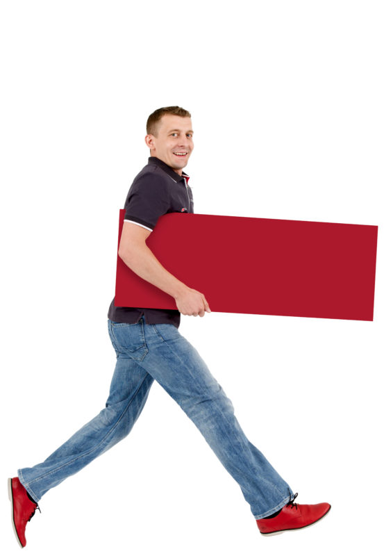 Employees photography: For a personnel campaign of a vehicle manufacturer, employees pose with a red sign against a white background. The photos are full body shots and each person acts differently in front of the camera. Here an employee walks with a long step through the picture.