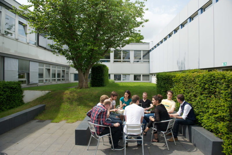 Science photography:  In a garden of the Max Planck Institute for Intelligent Systems, scientists discuss while sitting around a table.