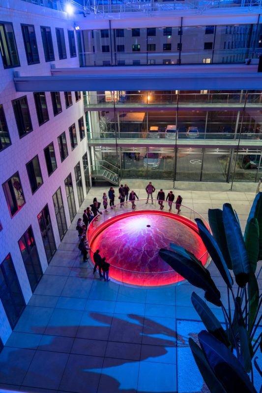 Architectural photography:  Interior view of the Fraunhofer Institute for Industrial Mathematics ITWM in Kaiserslautern. In the roofed atrium, visitors can stow the illuminated dome of the RODOS vehicle simulator in the basement below.