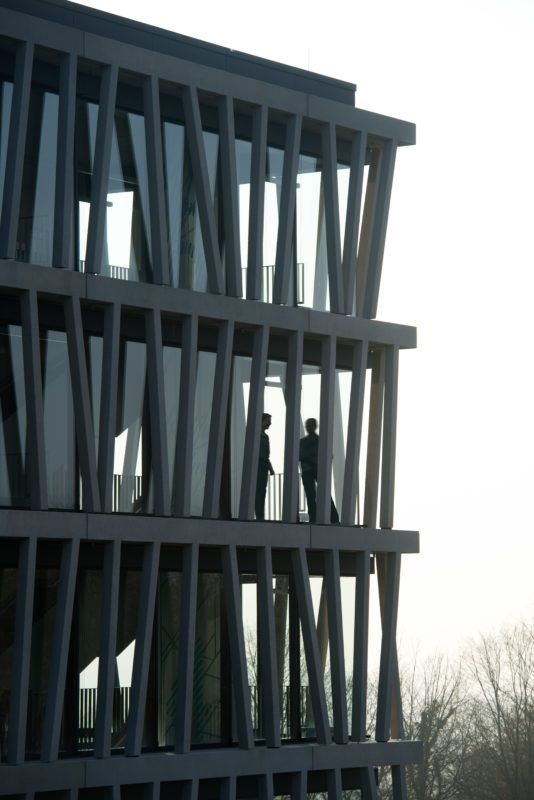 Architectural photography: Graphic exterior view of a part of a modern research institute building. Through the open facade structure one can see the silhouette of people in the building talking to each other.