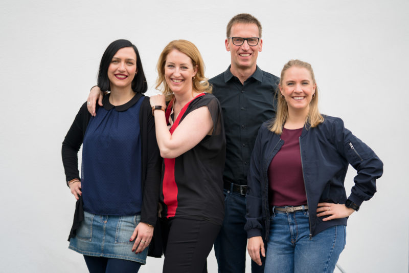 Group photo: Portrait of four speakers of an internal company event series, taken a few minutes before the start of the event in natural light and against a calm, bright background.