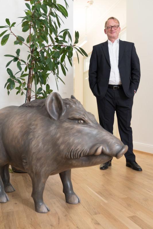 Managerportrait: Der geschaeftsfuehrende Vorstand in den Räumen einer Stiftung. Im Vordergrund sieht man ein Wildschwein aus Plastik, das an die Wälder erinnert, die von der Stiftung verwaltet werden.