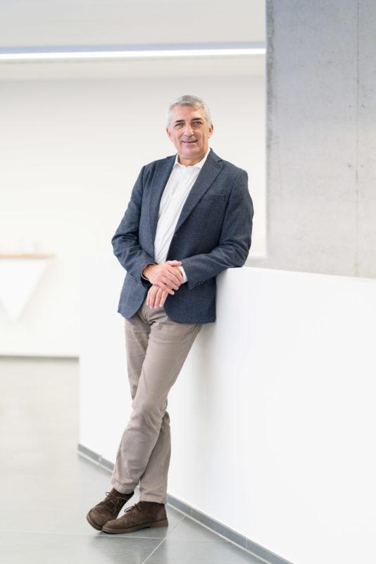 Managerportrait: Ein italienischer Geschäftsmann in blauem Sakko und beiger Hose lehnt lässig an einer Balustrade. Der große Raum in der Firma wirkt hell und freundlich.
