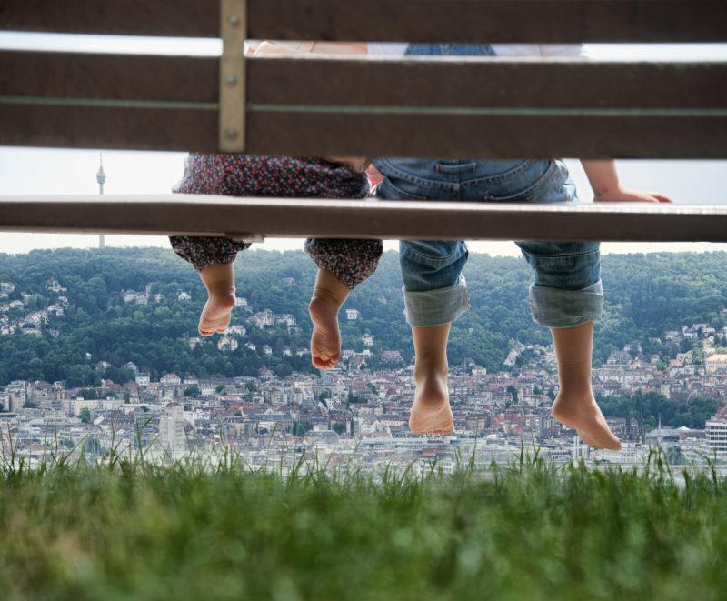 Reportagefotografie: Ein kleines Baby und sein älterer Bruder sitzen auf einer Bank im Freien und schauen in den Stuttgarter Talkessel. Auf dem Foto sieht man nur die Füße.