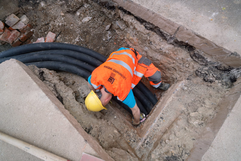 Industrial photography: Glass fibre lining: A construction worker sits in the trench dug on a sidewalk and seals an opening with freshly laid large empty pipes leading into an inspection shaft.