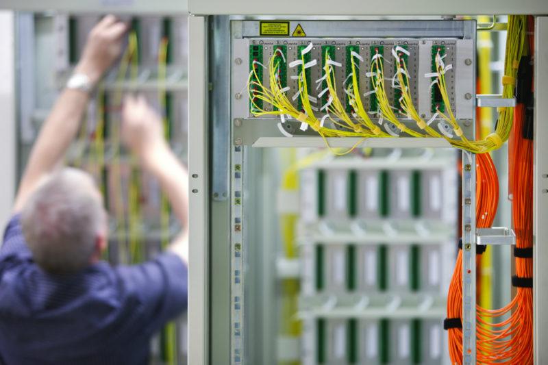 Industriefotografie: Ein Techniker der Deutschen Telekom AG verlegt Glasfaserkabel in einer Vermittlungsstelle.