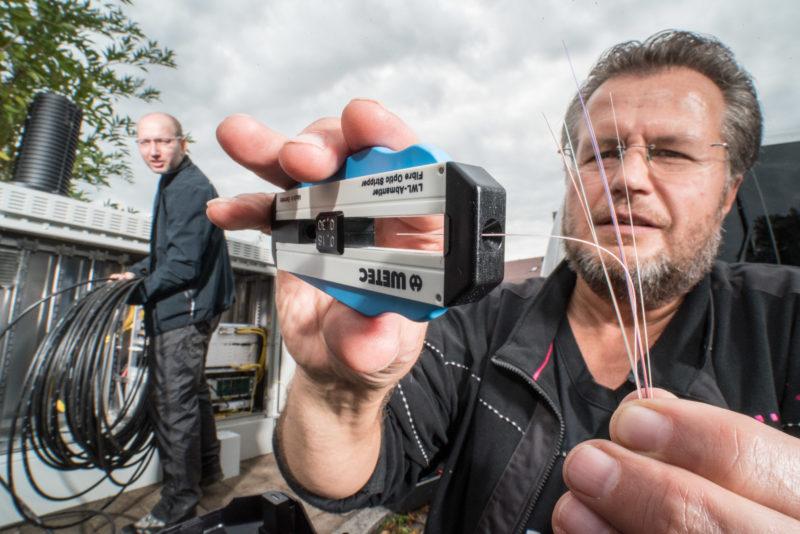Reportageotografie: Ein Techniker mantelt auf der Straße ein Glasfaserkabel ab, während ein Kollege im Hintergrund am Anschluss eines Verteilergehäuses für Breitbandinternetverbindungen arbeitet.